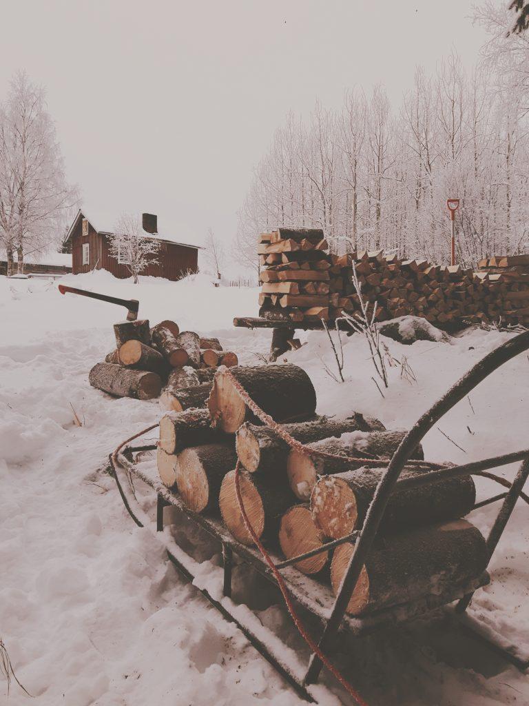 kulttuuriymparisto perinnemaisema puupino punainen tupa talvella mokki vanhanaikainen nostalgia halkopino puu polkky kirves fiskars x17 kainuu visit finland