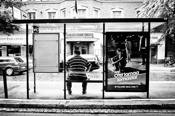 mustavalkoinen helsinki ratikkapysakki mies istuu odottaa