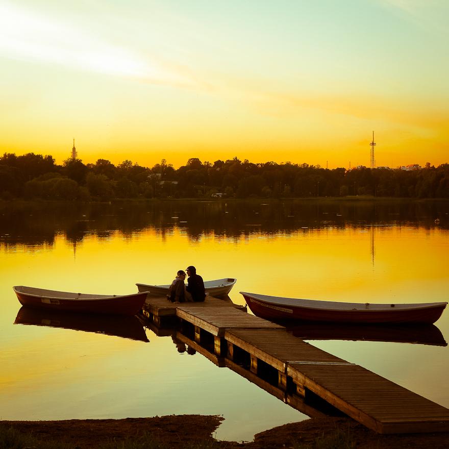 pariskunta toolonlahdella laiturilla auringonlasku tyyni ilta