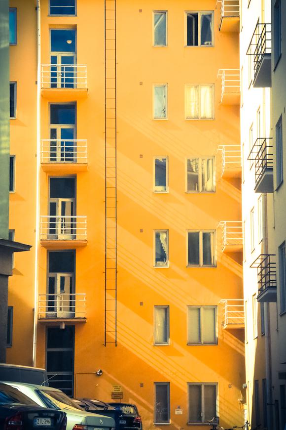 värikäs keltainen kerrostalo johon valo lankeaa parvekkeet ikkunat idyllinen sisäpiha helsinki piritori kallio