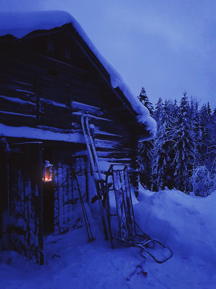 luminen-maisema-maaseutu-lyhty-ulkotuli-tunnelma-romantiikka-joulu-sauna-sininen-hetki-talvi-ilta-finland-moment-kelkka-metsa-sukset-reki-hirsi-rakennus