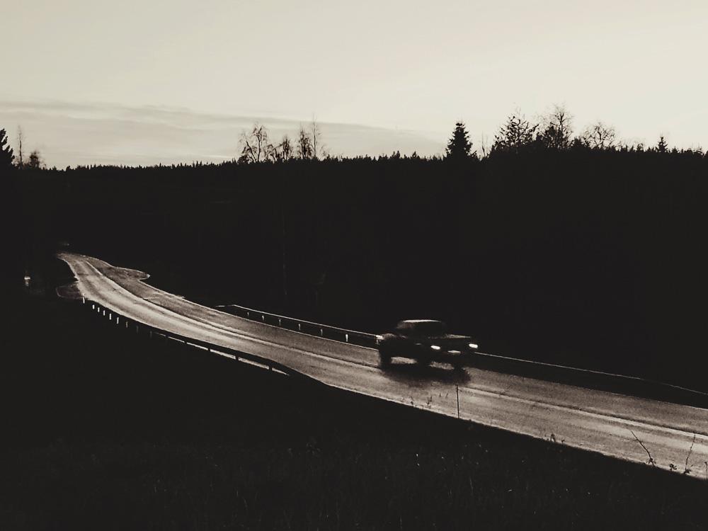 mustavalkoinen-tie-märkä-asfaltti-yksinäinen-auto-auto-ajaa-pois-päin-maisema