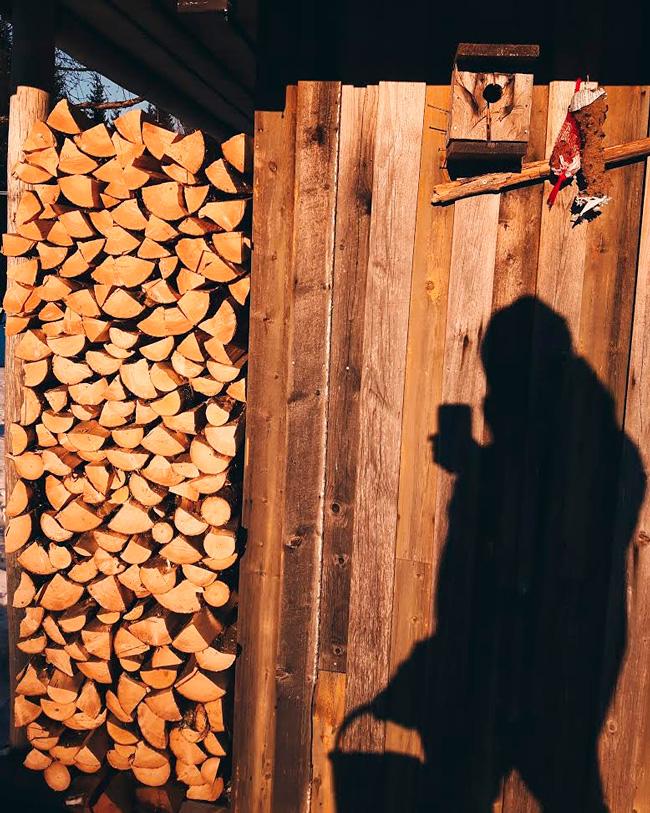puupino-firewood-stack-finland-aurinko-kevat-harmaa-seina-lautaseina-sauna-polttopuu-vanha-rakennus-linnunpontto-kainuu-sotkamo