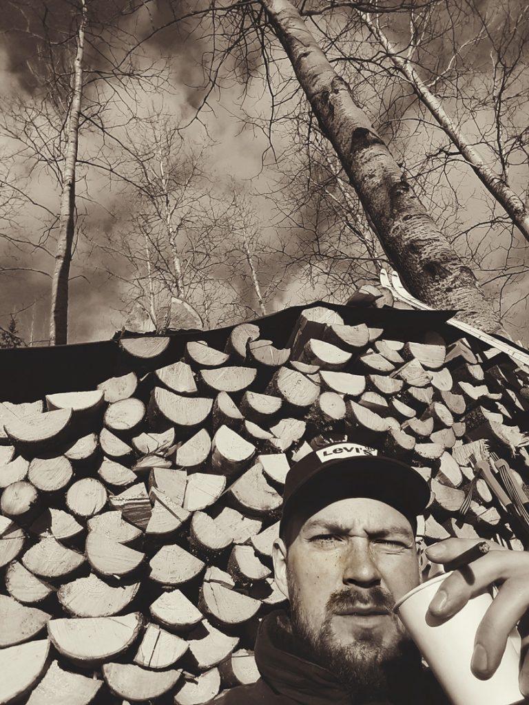slow-finland-kainuu-metsa-polttopuu-firewood-stack-selfie-pinoaminen-puiden-kevat-aurinko-haavikko-korkea-puu-taivas-kahvitauko-termospullo-2