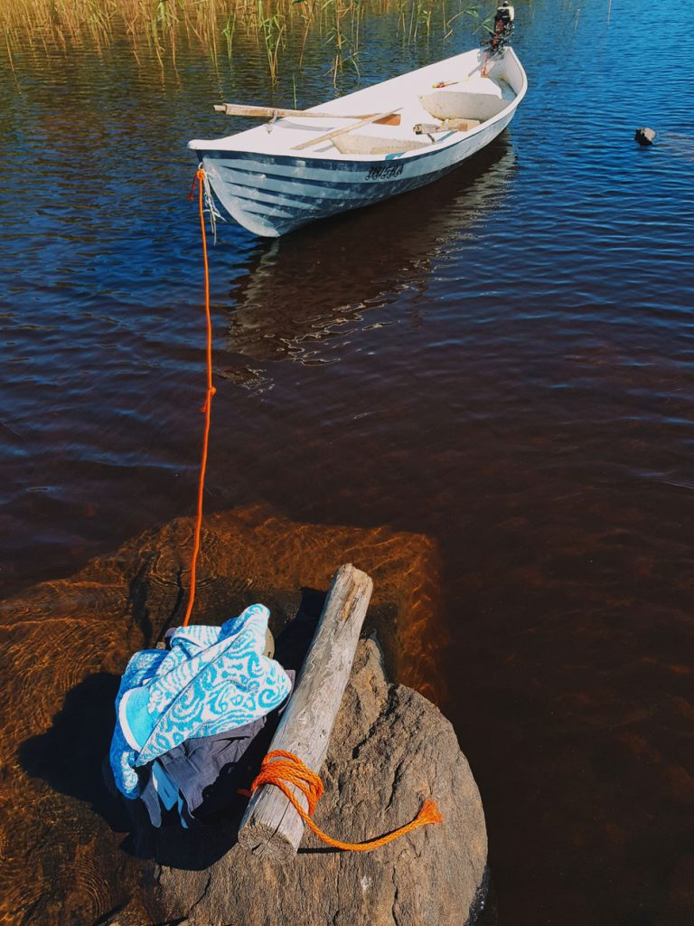kivi-karikko-uinti-pyyhe-lammin-kirkas-ja-puhdas-vesi-kesa-maaseudulla-puuvilla-veneen-parkkeeraaminen-kiinnitys-kivella-uimaan