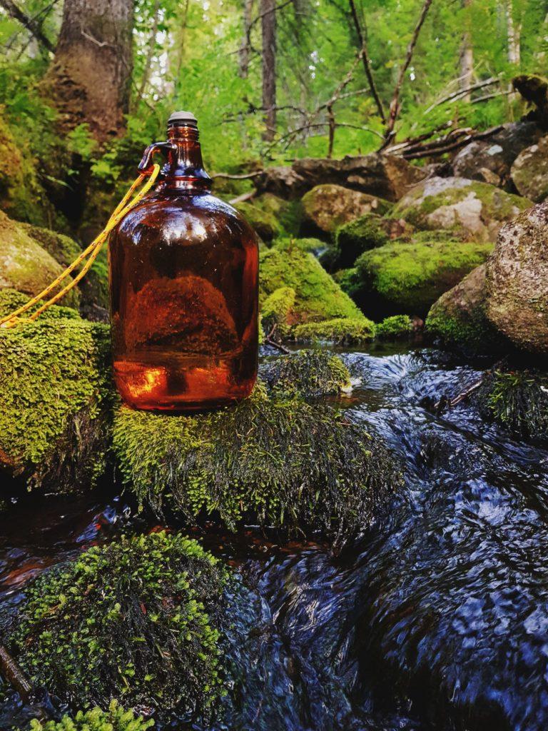 ruskea-lasipullo-luonnon-puro-lahdepuro-kivinen-soljuva-metsa-vesi-retkipaikka-valokuva-sotkamo-kainuu-vanha-metsa