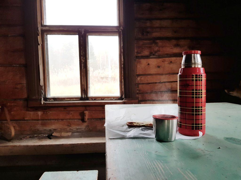 kahvi-termospullo-puinen-pirtin-poyta-kotiseutu-museo-hirsitalo-hirsiseina-vanhat-ikkunapokat-vanha-talo-kainuu