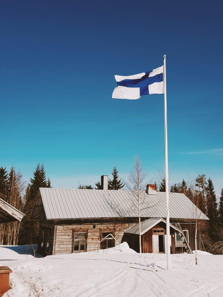 vanha hirsitalo lippu salossa perinnemaisema kevat auringossa pihapiiri vaara asutus kainuun