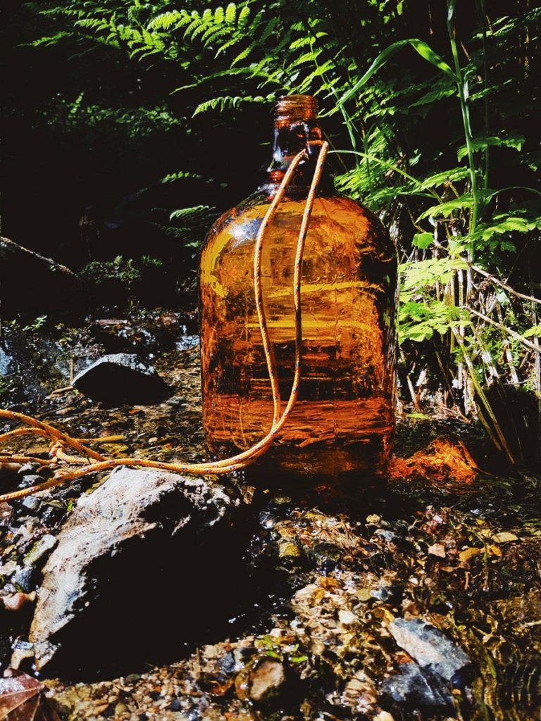 vesipullo-purossa-glass-brown-bottle-on-a-litte-creek-stream-water-lahde-vesi
