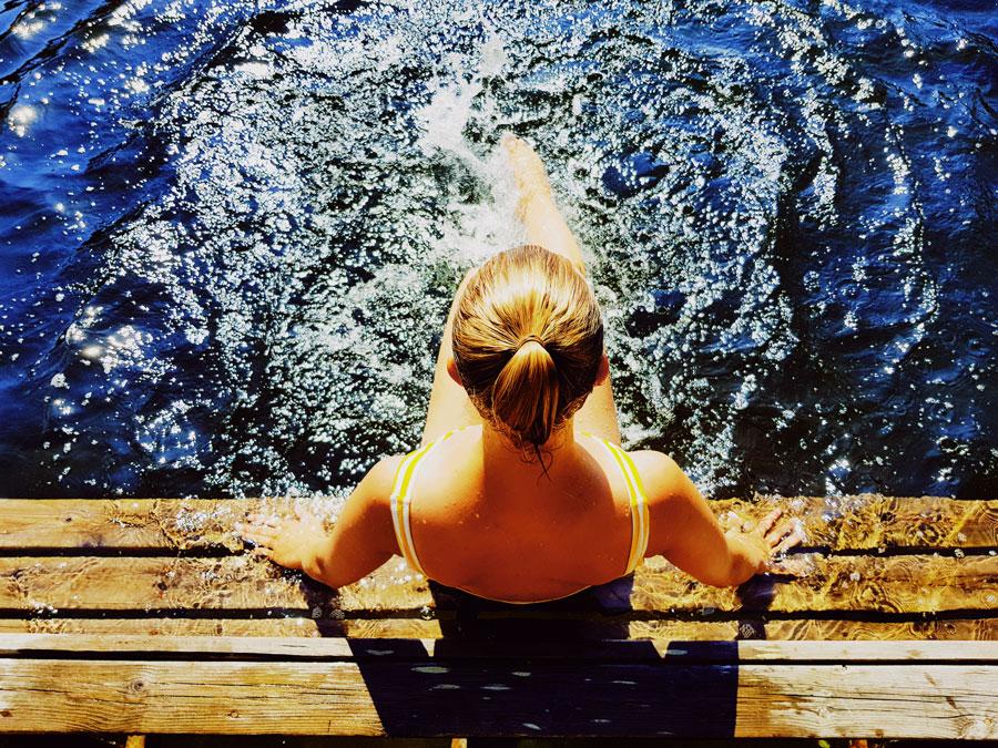 hellepaiva-uimalaiturilla-girl-sitting-pier-yellow-swimsuit-blue-water-sininen-vesi-heinakuu-kesaloma